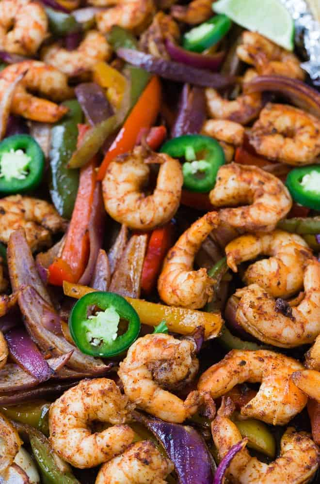 Close up view of sheet pan shrimp fajitas topped with fresh jalapeno peppers.