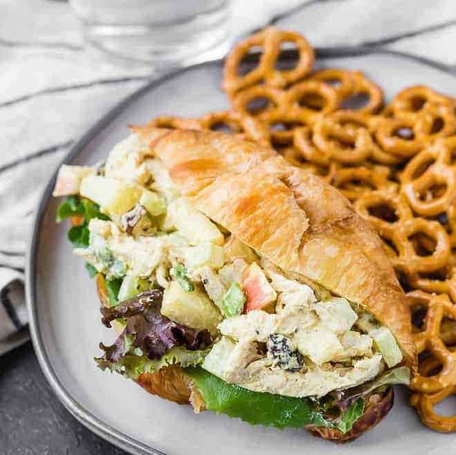 特写用酸奶做鸡肉沙拉,咖喱粉,苹果,葡萄干,和葱的图像上的新鲜面包羊角面包。