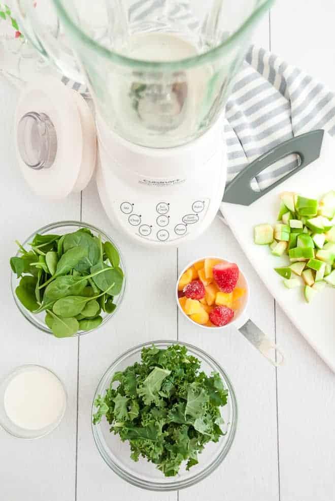 空搅拌器的俯视图,四周菠菜,羽衣甘蓝,热带水果和青苹果的碗。