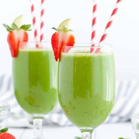两个绿色饮品与红色和白色的纸吸管朵朵眼镜。草莓配菜眼镜的边缘。