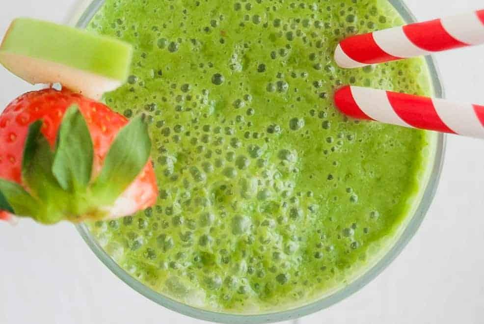 在玻璃绿色冰沙的俯视图,有一个红色的草莓和绿色的苹果切片摆盘。