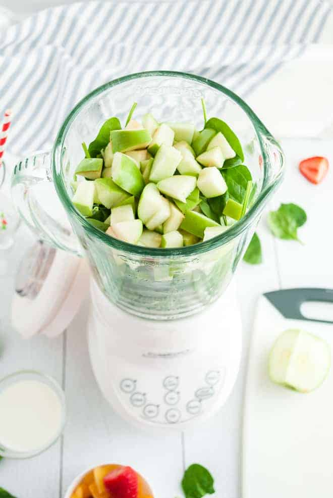 Overhead view of a white blender filled with greens and chopped green apples.