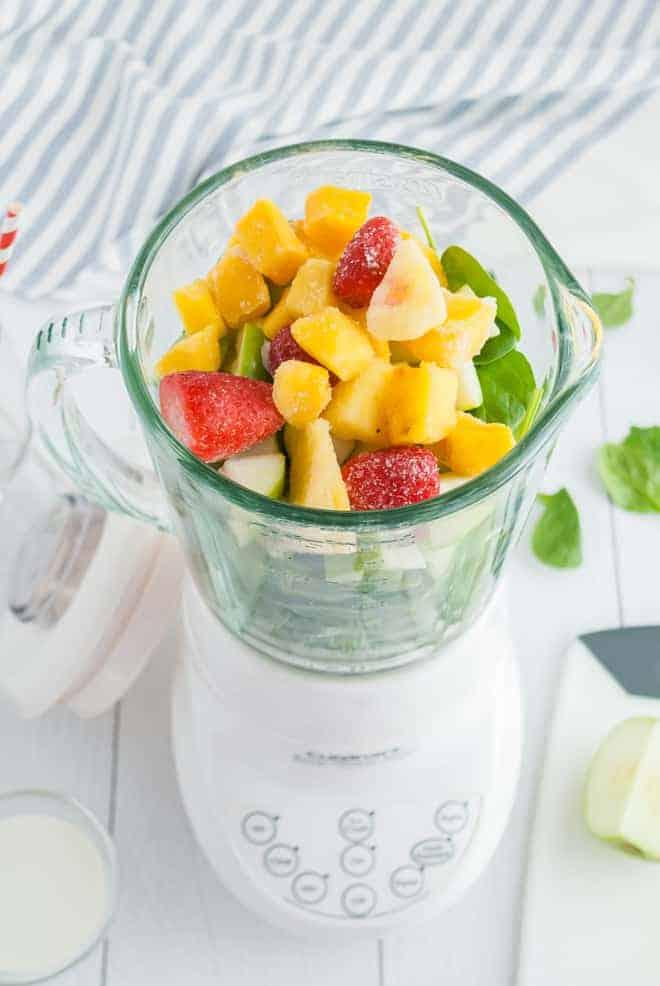 搅拌机的俯视图充满了绿色和冰冻的热带水果。