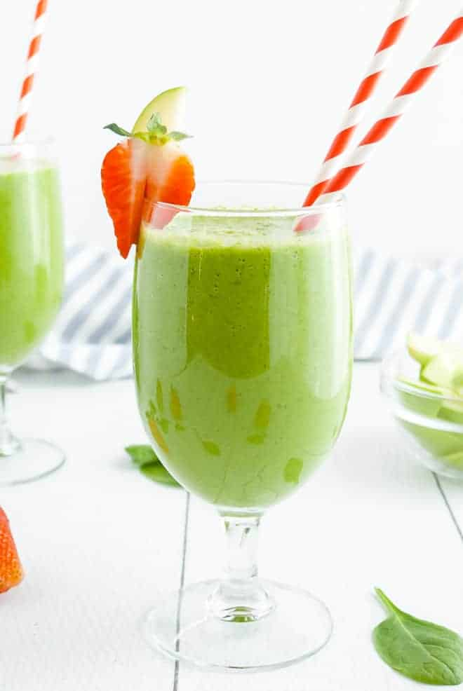 Green smoothie drink in a stemmed glass with two red and white striped paper straws.