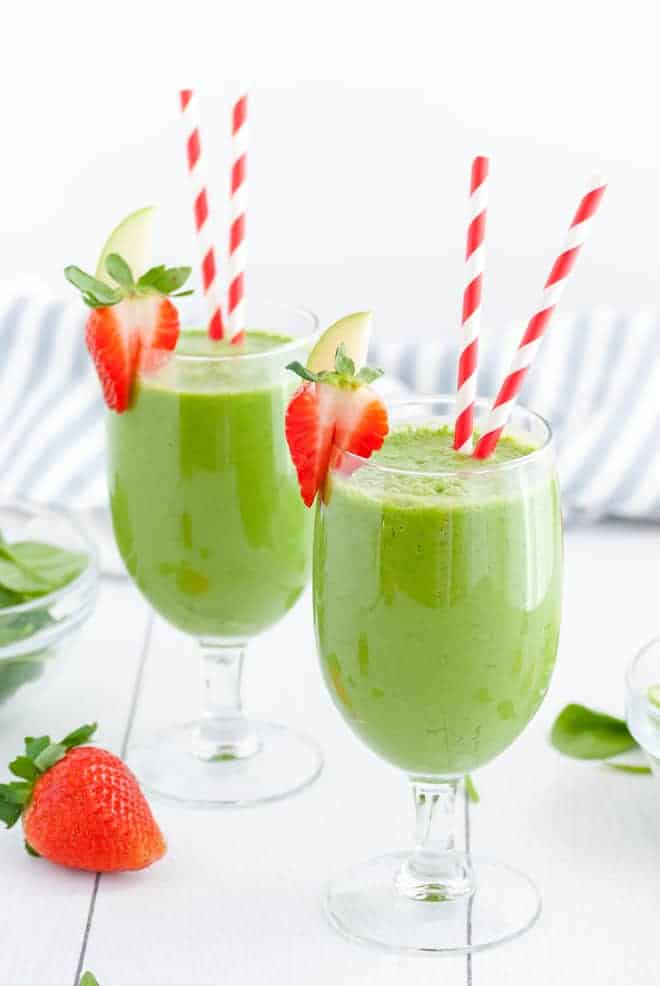 Two stemmed glasses, each with two red and white striped straws. Each glass is filled with green liquid and topped with fresh strawberries.