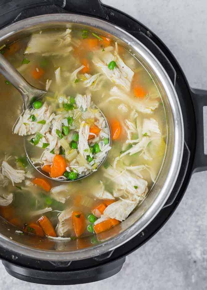 即时锅压力锅的俯视图充满了鸡肉,大米和蔬菜汤。钢包被舀出一些汤。