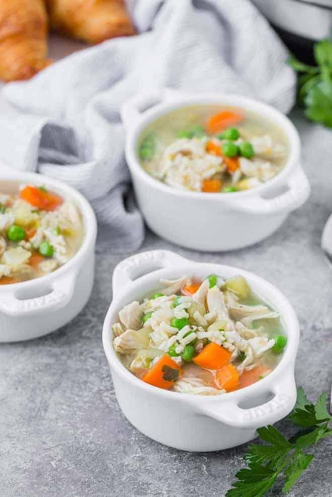 三个白小碗含汤鸡肉,米饭,蔬菜。牛角包被描绘在背景中。