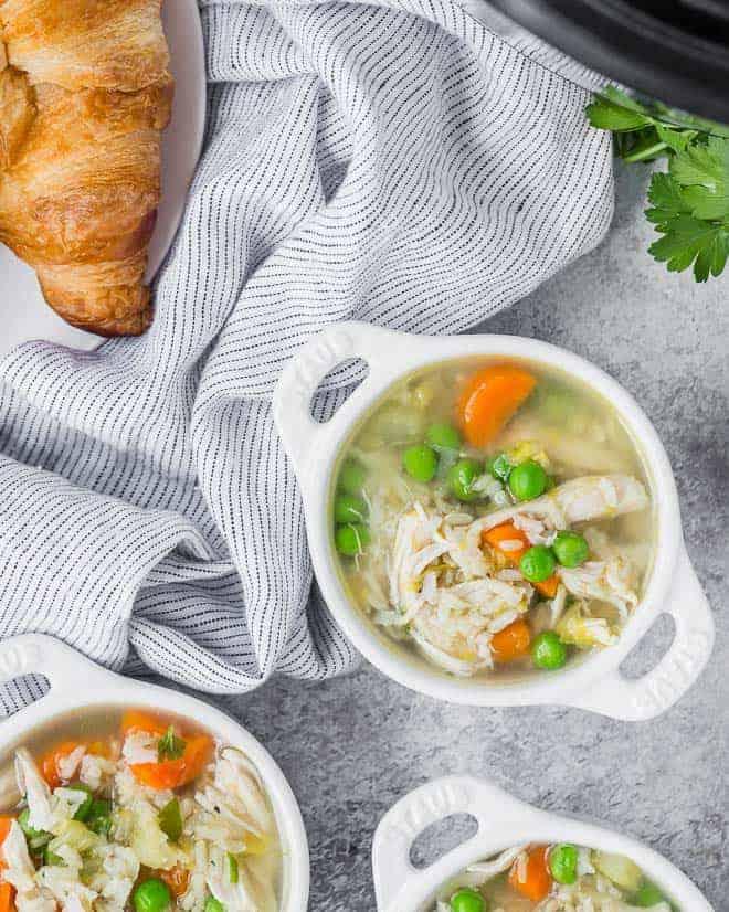 俯视图的大米和鸡汤,羊角面包,和即时锅压力锅的局部视图的三个小碗。