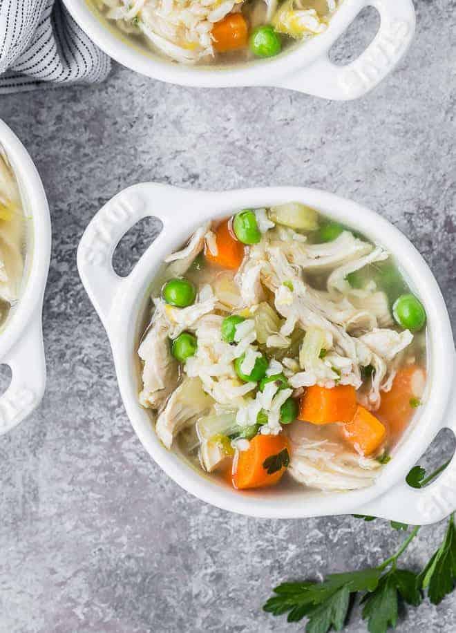 白色小碗鸡肉米汤俯视图与两个小手柄。汤另外两个碗部分合照。
