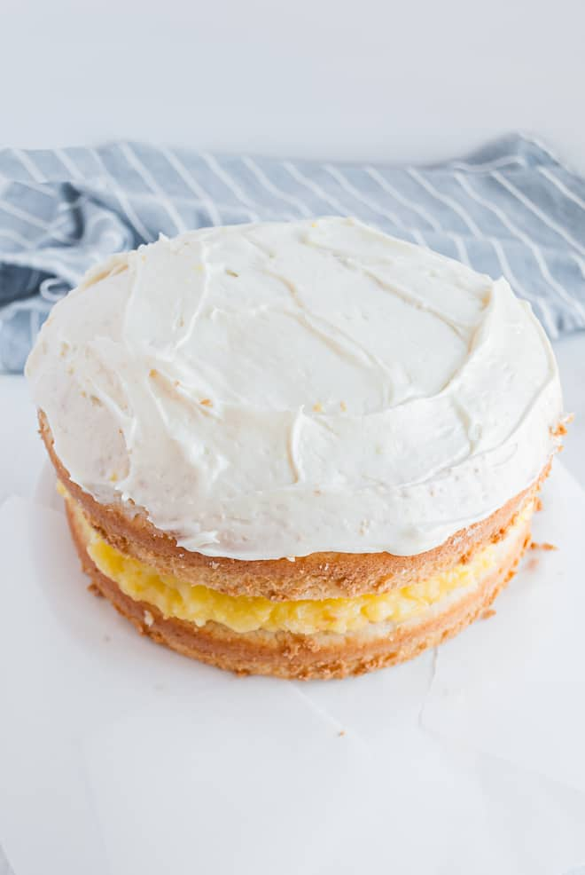 White cake with cream cheese frosting and lemon filling, halfway frosted.