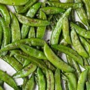 Image of roasted sugar snap peas on a sheet pan, seasoned with salt, pepper, and garlic powder.