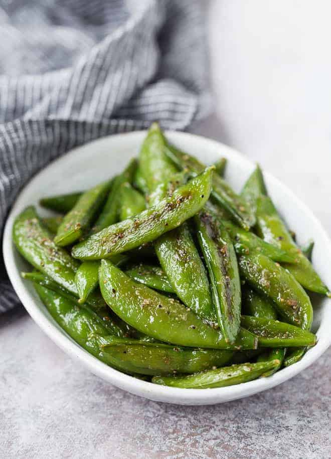 Image of sugar snap peas that have been perfectly roasted with olive oil, salt, pepper, and garlic powder.