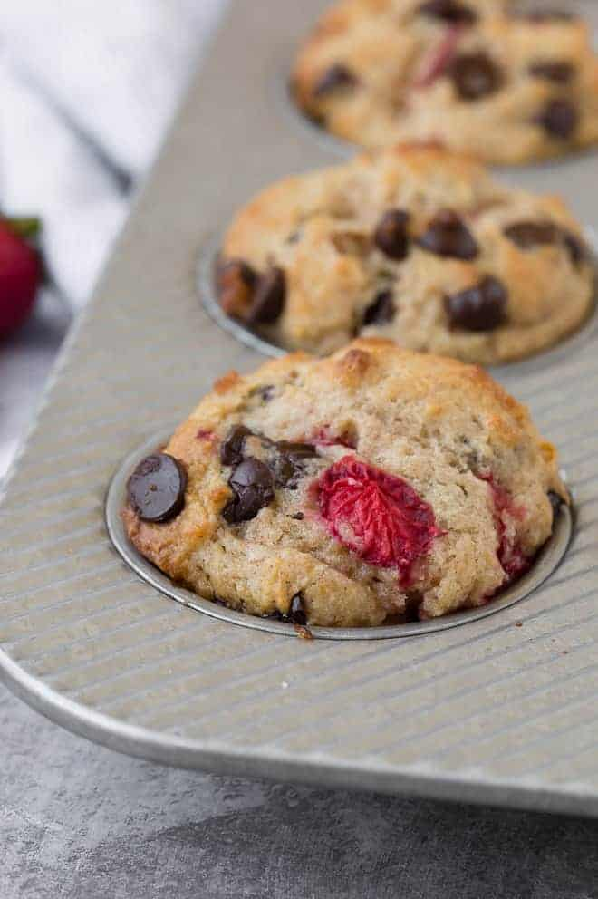 Close-up image of a muffin flecked with fresh strawberries and gooey dark chocolate chips. More strawberries and chocolate chips are pictured in the background.