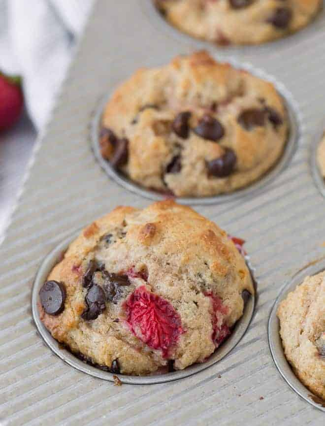 Image of muffins in a tin, flecked with strawberries and chocolate chips.