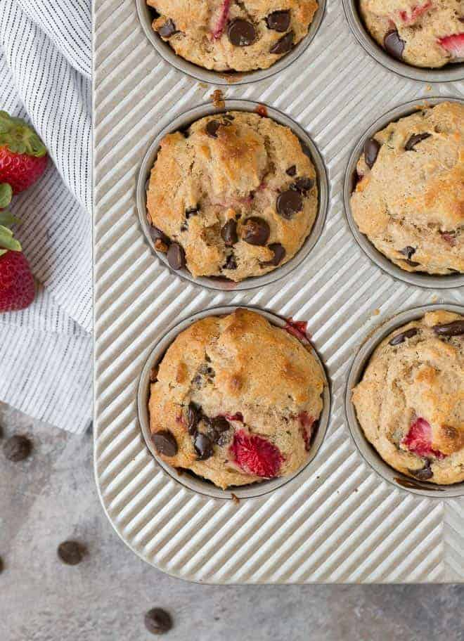 Overhead image of muffins in a tin. They are flecked with chocolate chips and strawberries, and there are extra chocolate chips and strawberries off to the side.