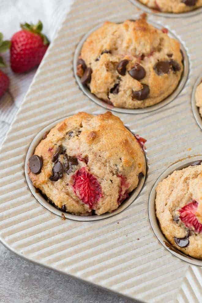 Image of fluffy whole wheat muffins with strawberries and chocolate chips in a muffin tin.