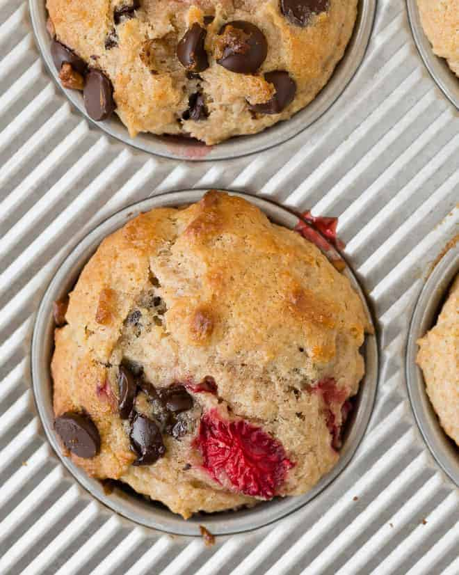 Overhead image of a strawberry muffin with chocolate chips in a baking tin.