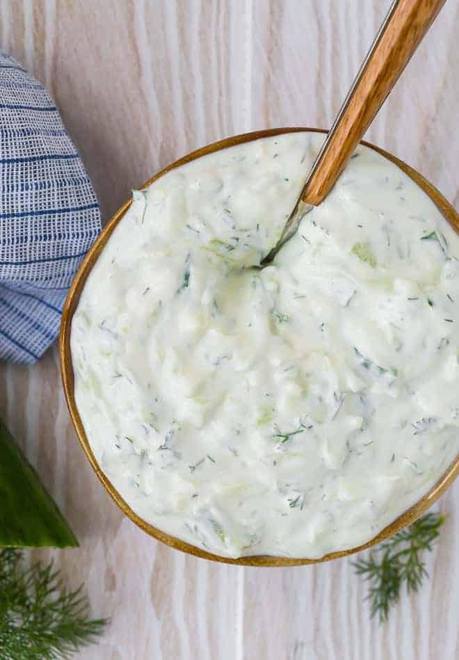 在一个碗里奶油酸奶酱的俯视图上一个木制的背景。黄瓜和莳萝放在围绕便盆。
