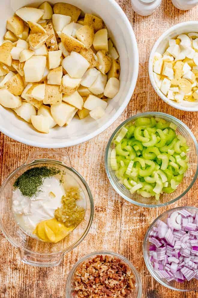 成分的碗,从上顺时针,煮熟切块的土豆,切碎煮鸡蛋的俯视图,切碎的芹菜,切碎的红洋葱,培根碎,最后一个碗装满了几个成分:蛋黄酱,芥末,津津乐道,莳萝。