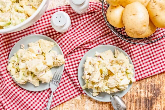 Two plates of creamy mayonnaise mustard potato salad on a red and white checkered cloth.