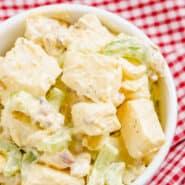 特写切块的土豆,芹菜,洋葱,培根,和煮鸡蛋一碗的俯视图在奶油淡黄色敷料用的绿色斑点翻腾。