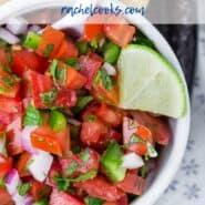"""西红柿,胡椒,并用文本覆盖洋葱的白瓷碗的俯视图,上面写着""""最好的微微德加洛"""""""