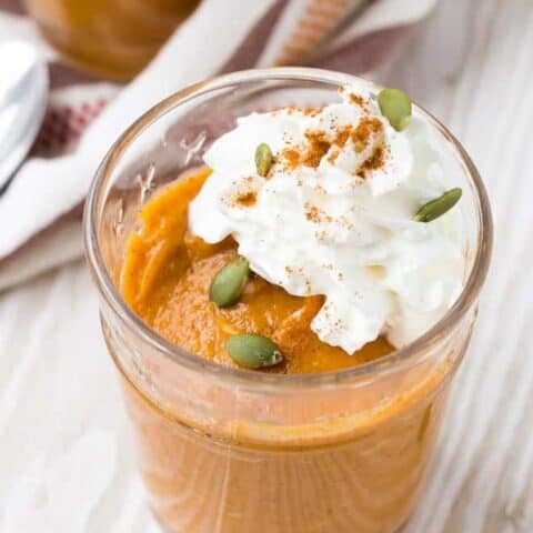 Close up view of easy pumpkin pudding garnished with whipped cream, pepitas, and cinnamon.