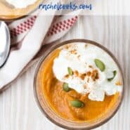 Overhead view of pumpkin pudding garnished with pumpkin seeds and whipped cream.