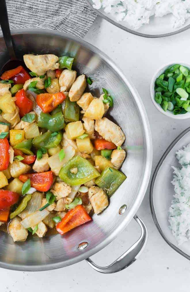 Overhead view of sweet and sour chicken in a silver wok. Plates of rice are also pictured, as well as a small bowl of chopped green onions.