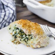 A breaded chicken breast on a double stacked white plate with a fork. Chicken is stuffed with feta and spinach. A baking dish and a blue and white linen are pictured in the background.