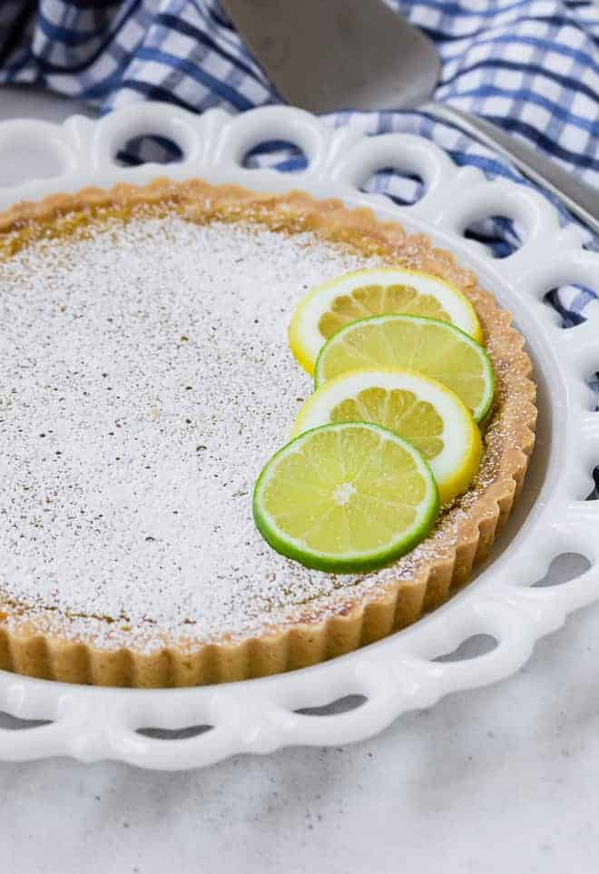 A white plate on a white marble background. On the plate is a tart topped with lemon and lime slices.
