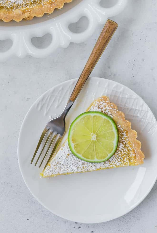 Overhead view of a slice of a tart topped with powdered sugar and a lime wheel.