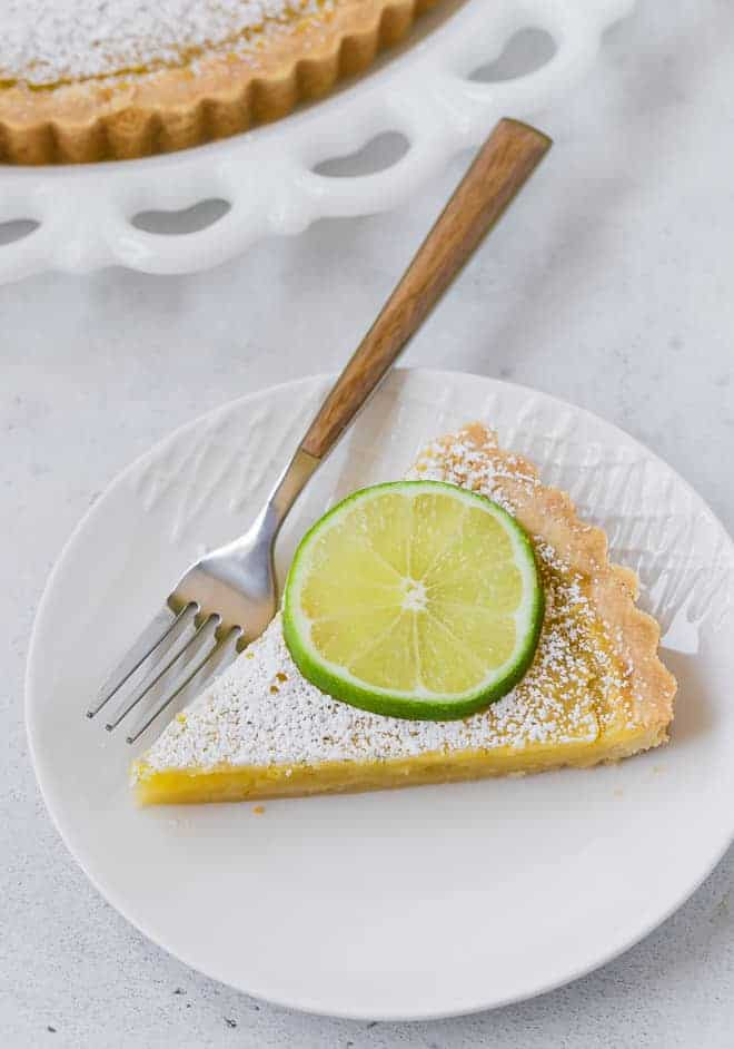 Slice of a lemon lime tart on a round white plate.