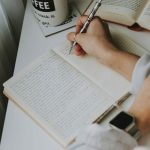 Hand poised holding a pen over a notebook next to a book and a cup of coffee