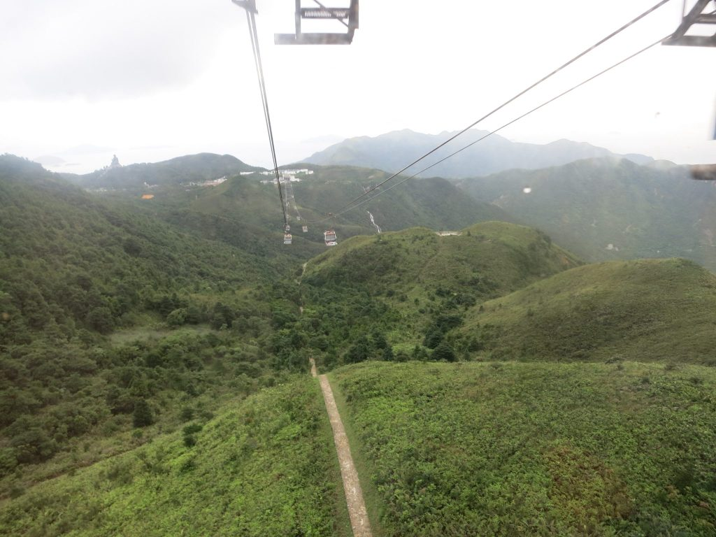a view over green hills from the cable car, with the Big Buddha on a hill in the distance