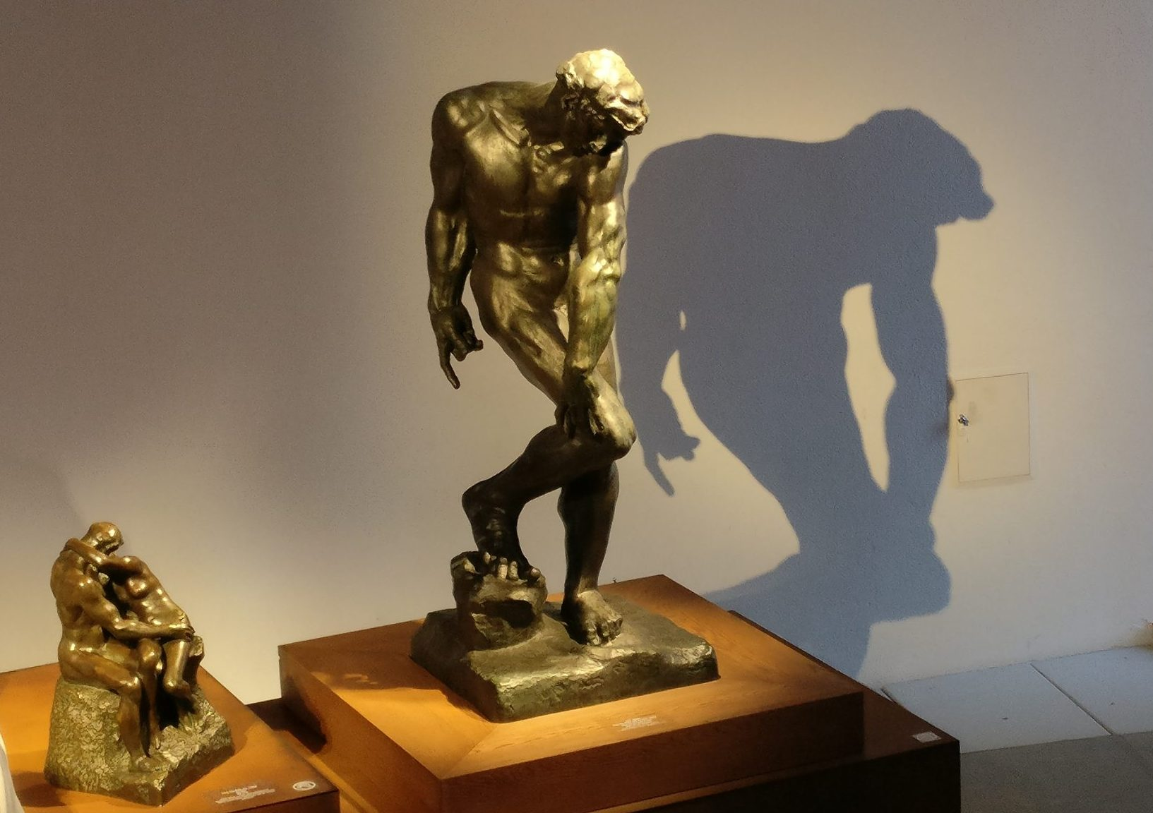 On the left, The Kiss in bronze from 1916. On the right, Adam, for The Gates of Hell, 1881, Rodin