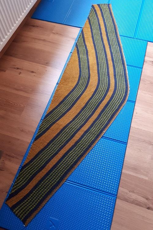 Tunisian crochet crescent shawl with Triskelion yarn on blocking mat