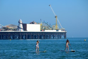 Paddle boarders enjoy the hot weather as evening falls