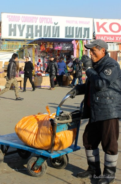 A market trader smokes at the entrance on Ulaanbataar's black market