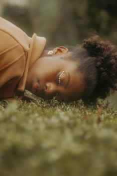 black female lying on grass in nature