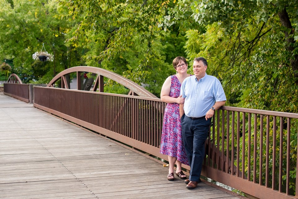 married couple posed together and leaning on the railing of a bridge