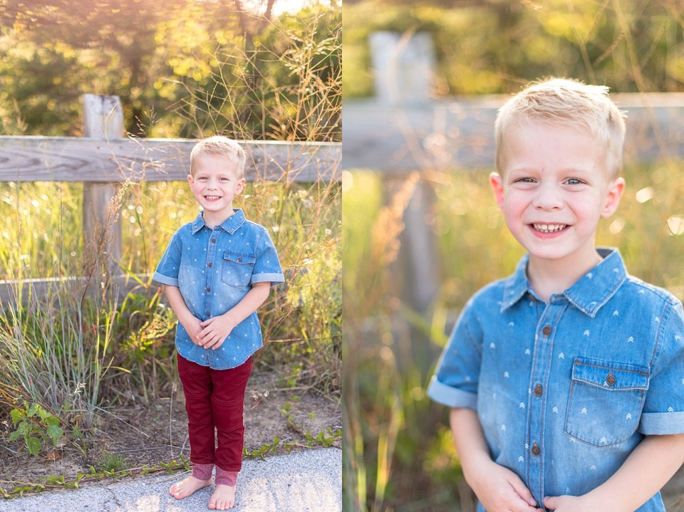 toddler portraits in a blue shirt and red pants by a wooden fence