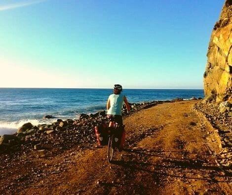 Rachel cycling on a stunning coastal road Cuba