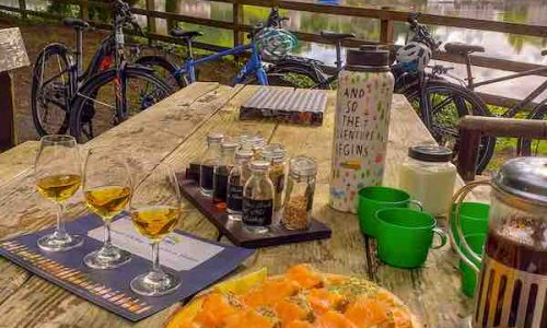 Picnic table at Belleek woods set with local produce from Ballina, Co. Mayo. Whiskey Tasting by Rachel's Irish Adventures and bicycles from Bikes2Rent in the background.