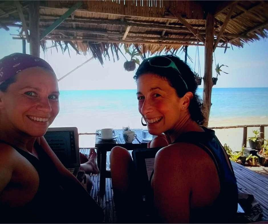 Iszy and Rachel working on trailor-made Ireland tours in a beach hut in Thailand