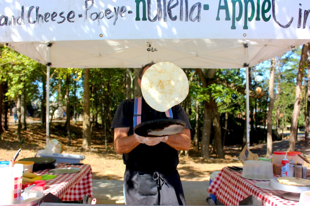 A man flips a crepe into the air as he prepares a customer's order at the Woodstock Farmer's Market on Oct. 8, 2016. This was one of the last farmer's markets of the season in Woodstock, Ga.