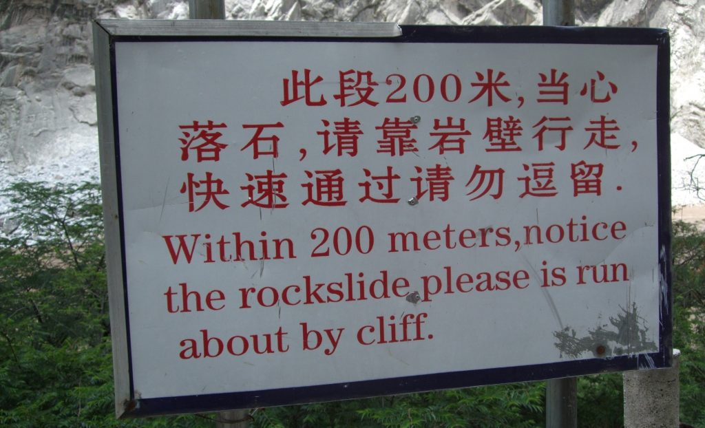 "sign reading ""Within 200 meters, notice the rockslide please is run about by cliff."""