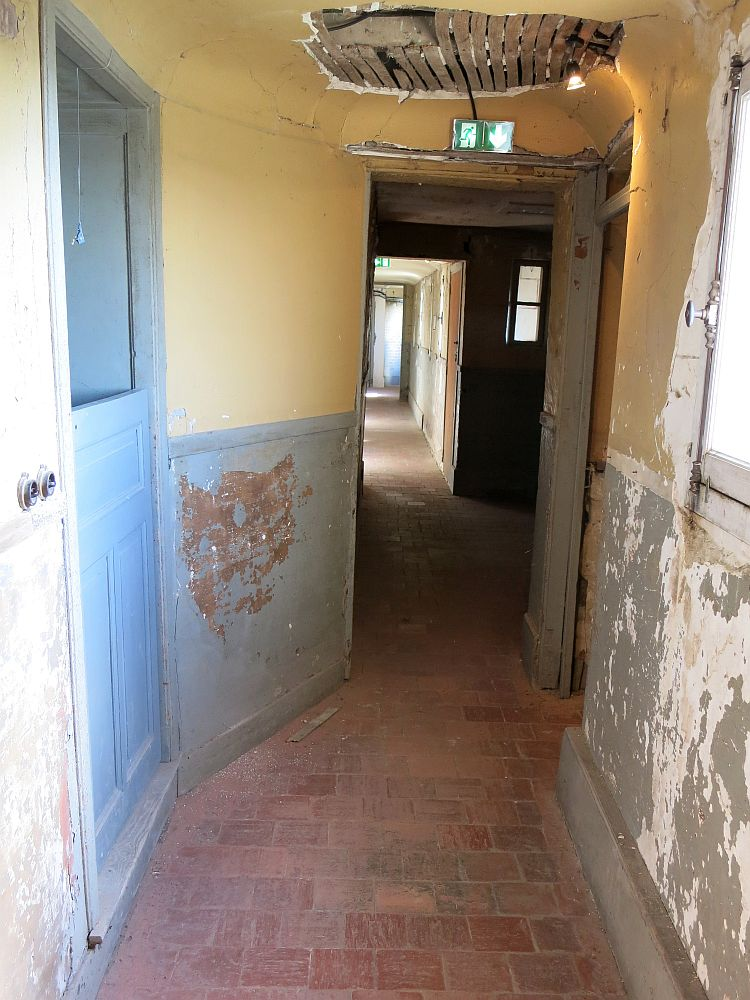 The hallway is in very poor condition: the walls are painted blue below and yellow above, but the paint is badly peeled and on one side the lower part of the wall - the wainscoting, has come off entirely. A patch on the ceiling is missing its plasterwork so the slats of wood are visible.