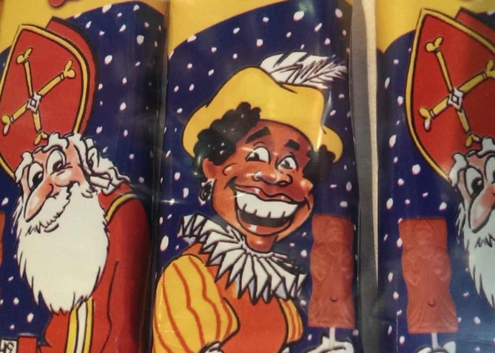In this close-up are 3 wrappers. On the left and right are images of Sinterklaas: a white man with a thick white beard, wearing a mitre like a bishop on his head: it's red with a gold cross. He smilles. IN the middle is a Black Piet with black skin, a big smile and curly black hair. He wears a yellow hat with a white feather in it. Around is neck is a big pleated white collor and his sleeves are puffy. What the Dutch think about Americans