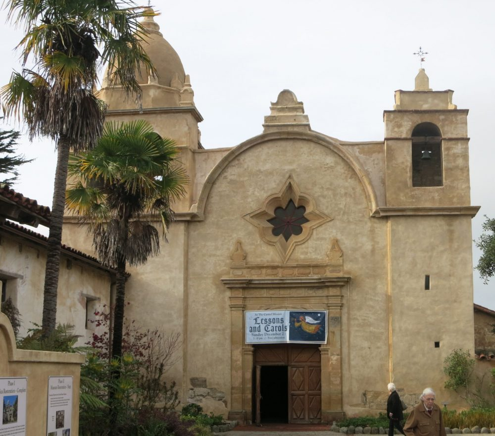front view of Carmel mission: light brown adobe, with a big entrance in the center, and a flower shaped recessed window right above the entrance. Two towers, but neither is very high. The left one has a small dome on it and the right hand one is square and doesn't protrude very far above roof level. Tall palm trees on the left next to the entrance.